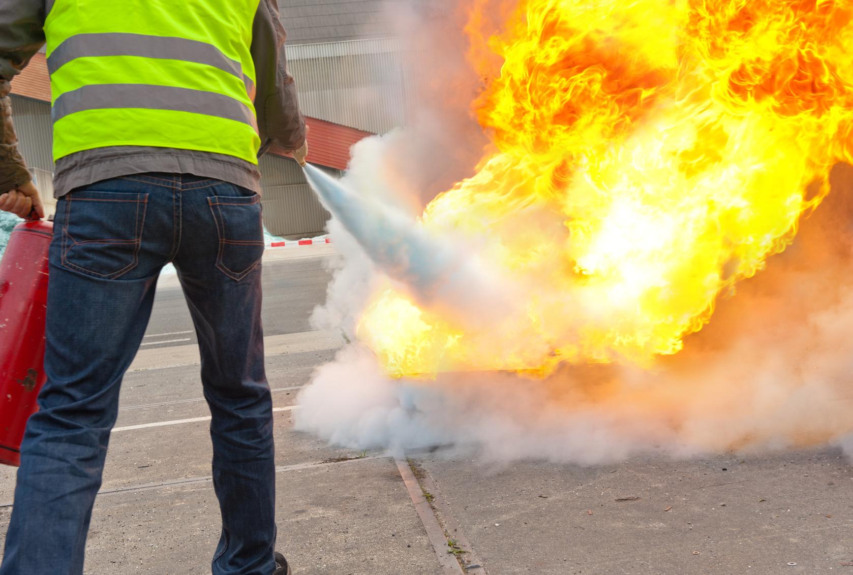 Mann löscht einen Brand mit Feuerlöscher